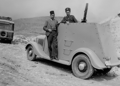 My father Yousef (his bus in the background) with a Palestinian armored border guard. (1945)