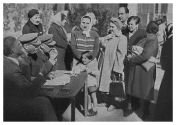 My mother Tuma (third from right, with handbag), in the Baq'a prison zone, waiting in line for food rations from UNRWA. (1948)